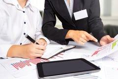 Kvinnliga händer som gör forskning på kontorsskrivbordet, under affärsmöte Arkivbild