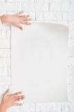 Kvinnliga händer som hänger den tomma affischen till väggmodellen Arkivfoto