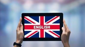 Kvinnliga händer som håller pekskärm med engelska ord mot brittisk flagga, online-app stock video