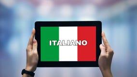 Kvinnliga händer som håller pekskärm med italienska ord mot nationell flagga, online-app stock video