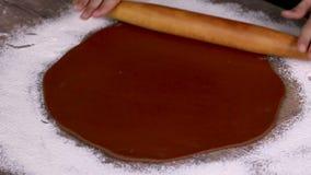 Kvinnliga händer som rullar ljust rödbrun deg på en trätabell Traditionellt baka för jul stock video