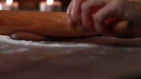 Kvinnliga händer som rullar ljust rödbrun deg på en trätabell Traditionellt baka för jul lager videofilmer