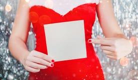 Kvinnliga händer som rymmer den glade julkortet eller bokstaven till jultomten Tema för Xmas och för nytt år royaltyfri foto
