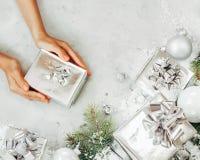 Kvinnliga händer som rymmer den närvarande asken Gåvor, granträdfilialen och garneringar på grå färger stenar tabellen Festlig ba royaltyfria bilder