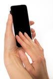 Kvinnliga händer som rymmer den smarta telefonen Arkivfoto