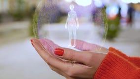 Kvinnliga händer som rymmer ett begreppsmässigt hologram med kvinnakroppen stock illustrationer