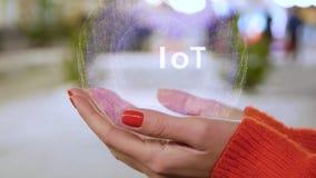 Kvinnliga händer som rymmer ett begreppsmässigt hologram med text IoT lager videofilmer