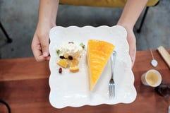 Kvinnliga händer som rymmer ett stycke av den orange kakan i en vit platta på dinning bästa sikt för tabell arkivfoto