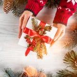 Kvinnliga händer som rymmer julgåvaasken på vit träbakgrund med granfilialer, sörjer kottar Tema för Xmas och för lyckligt nytt å royaltyfri foto