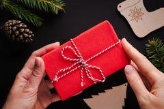 Kvinnliga händer som rymmer julgåvan slågen in i rött papper arkivbilder