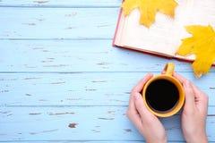 Kvinnliga händer som rymmer koppen av svart kaffe med den höstsidor och boken på den blåa tabellen royaltyfri foto