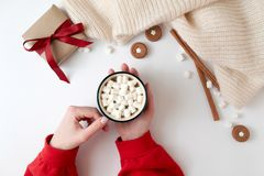 Kvinnliga händer som rymmer koppen av varm choklad med marshmallowen Juldryck, smakliga kakor, gåvaask på vit bakgrund arkivbild