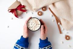 Kvinnliga händer som rymmer koppen av varm choklad med marshmallowen Juldryck, smakliga kakor, gåvaask på vit bakgrund flicka arkivbild