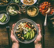 Kvinnliga händer som rymmer med den sunda vegetariska bunken med olik grillad grönsak-, avokado- och kikärthummus royaltyfri foto