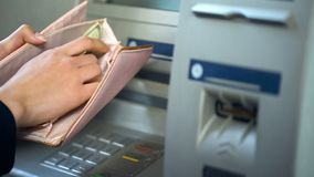 Kvinnliga händer som sätter dollar i plånboken, kassa som återtas från ATM som reser fotografering för bildbyråer