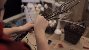 Kvinnliga händer som sammanfogar trästänger med en blå tråd som gör kransen