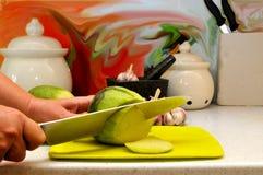 Kvinnliga händer som skivar med en stor kökkniv arkivfoton