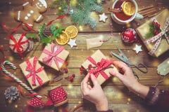Kvinnliga händer som slår in jul, semestrar handgjorda gåvor Royaltyfri Fotografi