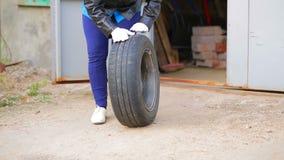 Kvinnliga händer som ut rullar ett bilgummihjul med en diskett ut ur garaget lager videofilmer