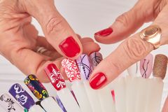 Kvinnliga händer som väljer, spikar design Fotografering för Bildbyråer