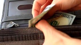 Kvinnliga händer tar ut hundra dollar från plånboken arkivfilmer
