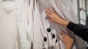 Kvinnliga händer trycker på skjortor i hängare i lager Kvinnashoose någon kläder, slut upp arkivbild