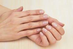 Kvinnliga händer utan fernissa spikar på Royaltyfria Bilder