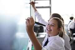 Kvinnliga högstadiumstudenter som bär enhetliga användande växelverkande Whiteboard under kurs arkivbild