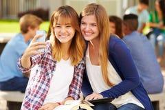 Kvinnliga högstadiumstudenter som tar Selfie på universitetsområde Arkivbilder