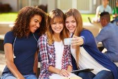 Kvinnliga högstadiumstudenter som tar Selfie på universitetsområde Arkivfoto