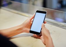 Kvinnliga h?nder som rymmer smartphonen med den vita sk?rmen arkivbilder