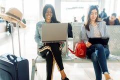 Kvinnliga handelsresande som väntar på avvikelse i flygplats royaltyfria foton