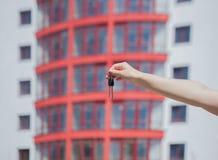 Kvinnliga handinnehavtangenter på bakgrunden av det nya huset verkligt begreppsgods Tangenter till den nya lägenheten Flytta sig  Royaltyfri Bild