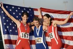 Kvinnliga idrottsman nen med amerikanska flaggan och medaljer Royaltyfri Foto