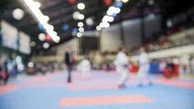 Kvinnliga karatekas slåss på karatekonkurrenser, de-fokuserad sportbakgrund stock video