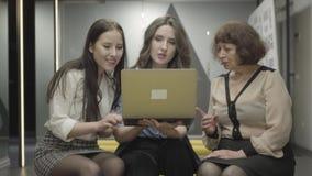 Kvinnliga kollegor som sitter ha tillsammans avbrottet på arbete Unga och mogna kvinnor som pratar bak baksidor av medarbetare arkivfilmer