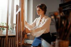 Kvinnliga konstnärarbeten på staffli i studio royaltyfria foton