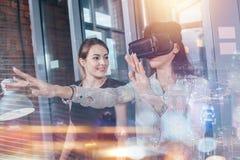 Kvinnliga kontorsarbetare som har gyckel på arbete som håller ögonen på videoen 3d i VR, rullar med ögonen, kvinnan som trycker p Fotografering för Bildbyråer