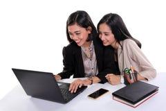 Kvinnliga kontorsarbetare som tillsammans använder bärbara datorn royaltyfria bilder