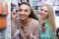 Kvinnliga kunder som väljer mascara Fotografering för Bildbyråer