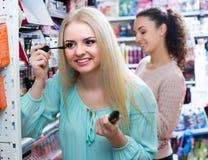 Kvinnliga kunder som väljer mascara Arkivbild