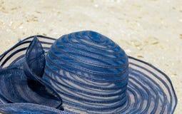 kvinnliga lögner för hatt för blått för sugrörhatt på sanden gjuter en skugga på ljusa ferier för en dagstrand Arkivbild
