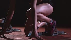 Kvinnliga löpare på friidrott spårar att huka sig ned på startgropen för ett lopp i ultrarapid lager videofilmer