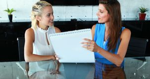 Kvinnliga ledare som diskuterar över diagram på skrivbordet 4k arkivfilmer