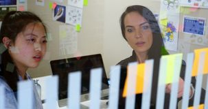 Kvinnliga ledare som diskuterar över en klibbig anmärkning 4k stock video