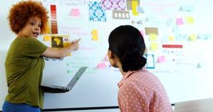 Kvinnliga ledare som diskuterar över klibbiga anmärkningar på whiteboard arkivfilmer