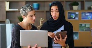 Kvinnliga ledare som diskuterar på bärbara datorn och den digitala minnestavlan 4k arkivfilmer