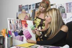 Kvinnliga modeformgivare som arbetar på skrivbordet Royaltyfri Fotografi
