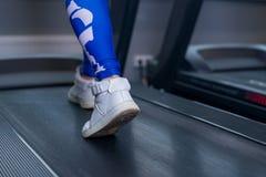 Kvinnliga muskulösa ben på trampkvarnen i sportidrottshall Begrepp för att öva, kondition och sund livsstil Fotografering för Bildbyråer