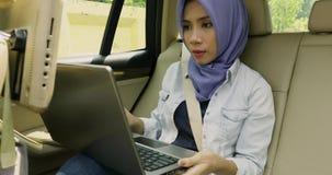 Kvinnliga muslim som arbetar med bärbara datorn i bil stock video
